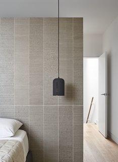 In the couple's bedroom, a Gap pendant from Woud hangs in front of a wall clad in STI Otto porcelain tile from Stone Tile.