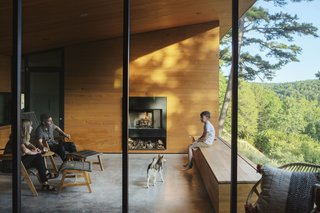 Owners Leah and Dan Curry and their son enjoy the semi-enclosed porch that looks out onto the hillside. The floor-to-ceiling windows are by Ozark Mountain Glass and Razorback Ironworks. The fireplace surround is also by Razorback Ironworks.