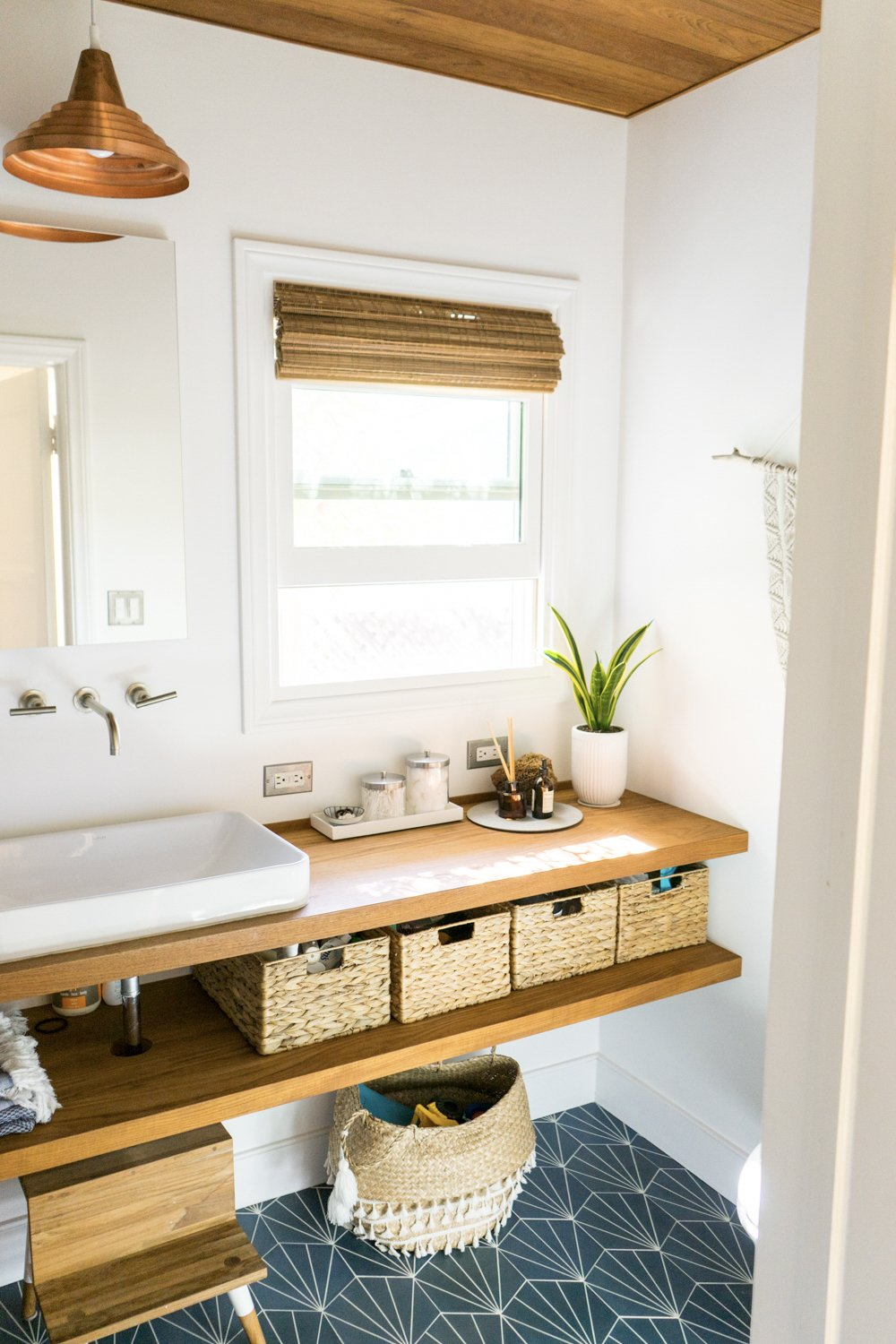 "The bungalow's bathroom has been updated with a custom vanity and copper light fixture.  Photo 15 of 17 in The ""Surf Shacks"" Author Lists His Venice Bungalow and Backyard Guesthouse for $1.6M"