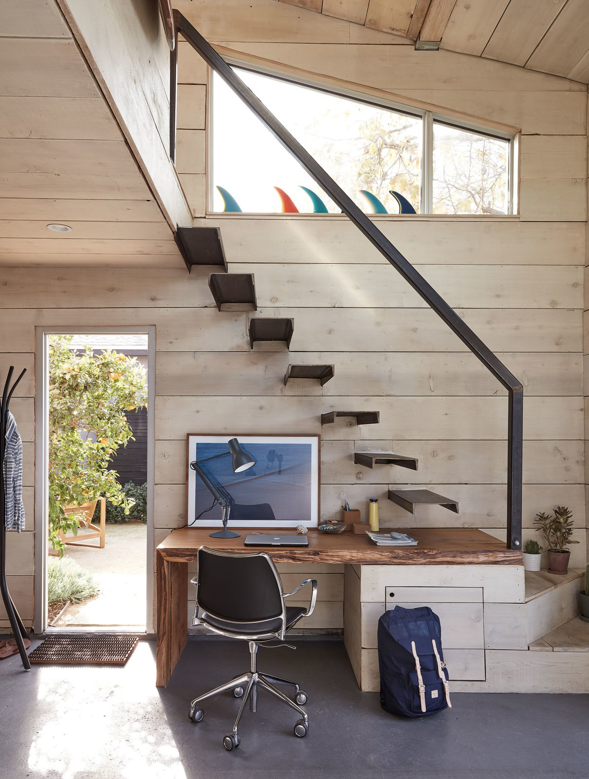 """Matt's brother, Sam, also fabricated the custom steel railing and floating stair treads. Underneath the stairs, a desk is built into the landing.  Photo 3 of 17 in The """"Surf Shacks"""" Author Lists His Venice Bungalow and Backyard Guesthouse for $1.6M"""