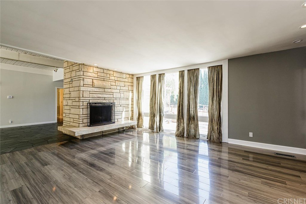 Opposite the entryway, the family room previously offered a large window but no access to the front deck.  Photo 16 of 25 in Before & After: Two Brothers List Their Swanky Midcentury Bachelor Pad for $1.6M