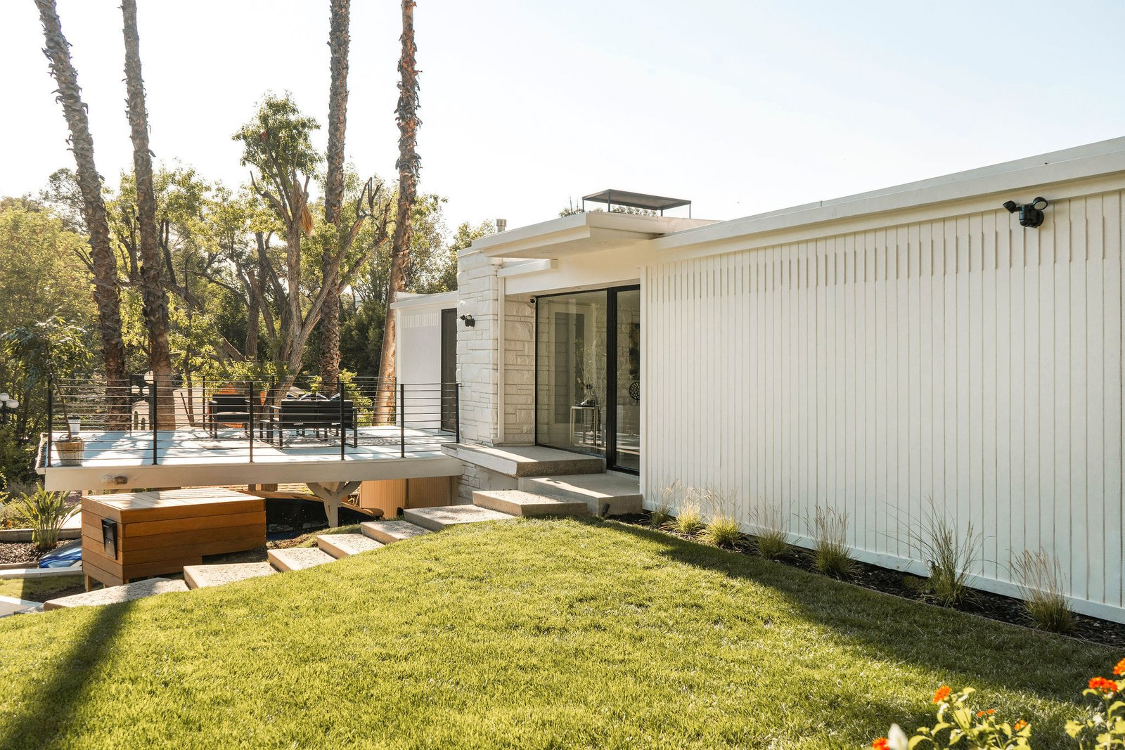 After, a white paint job, new landscaping and fixtures, as well as the addition of several glass doors give the facade a new look.  Photo 4 of 25 in Before & After: Two Brothers List Their Swanky Midcentury Bachelor Pad for $1.6M