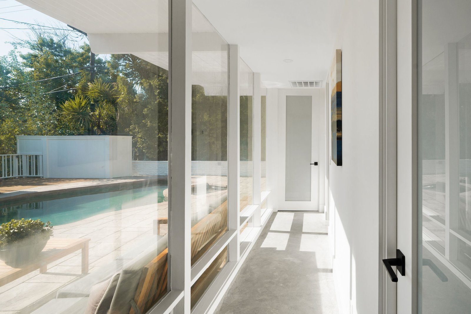 A glass-walled hallway connects several of the bedrooms with the main living area.  Photo 22 of 25 in Before & After: Two Brothers List Their Swanky Midcentury Bachelor Pad for $1.6M