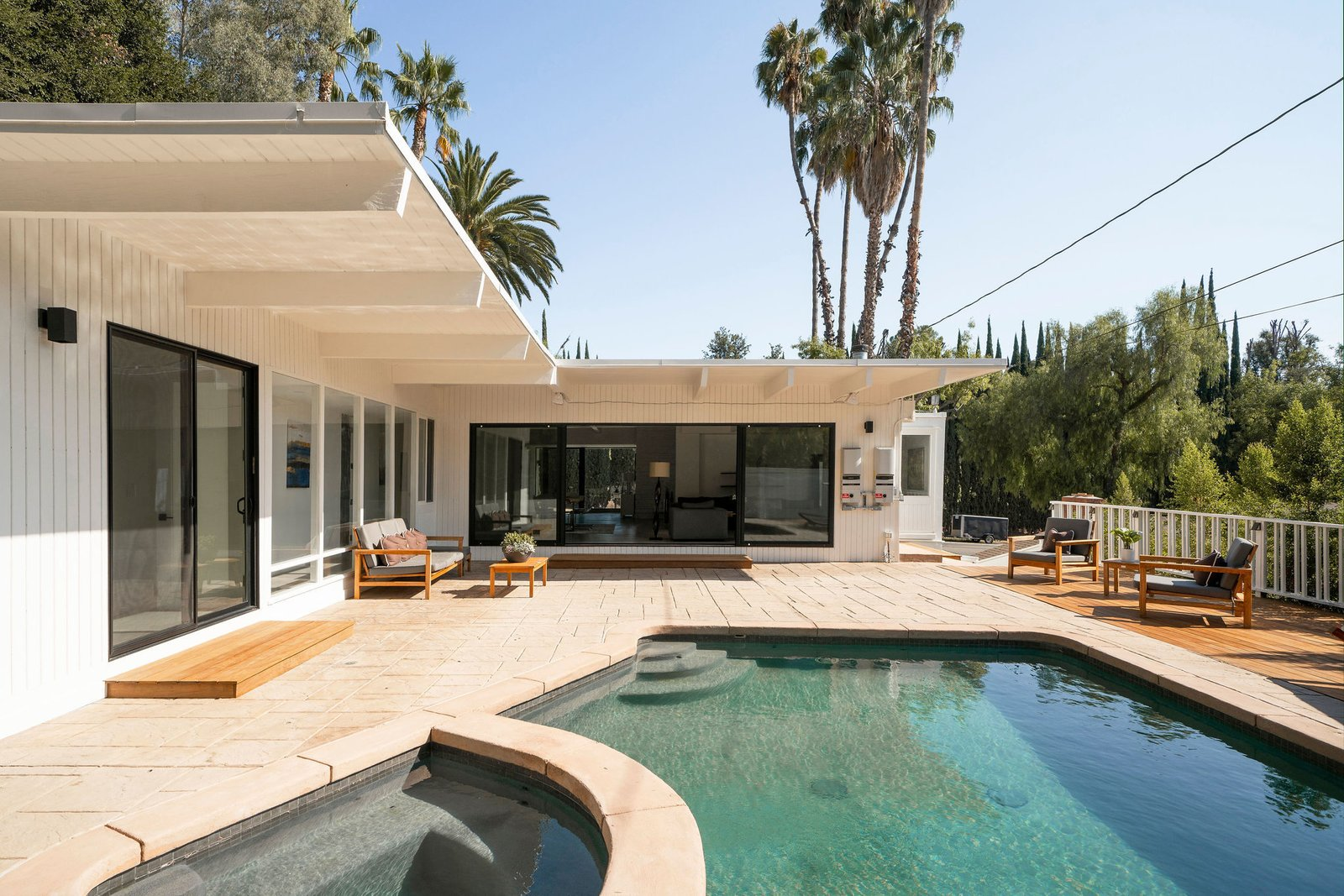 A resurfaced pool and new deck fill the backyard.  Photo 24 of 25 in Before & After: Two Brothers List Their Swanky Midcentury Bachelor Pad for $1.6M