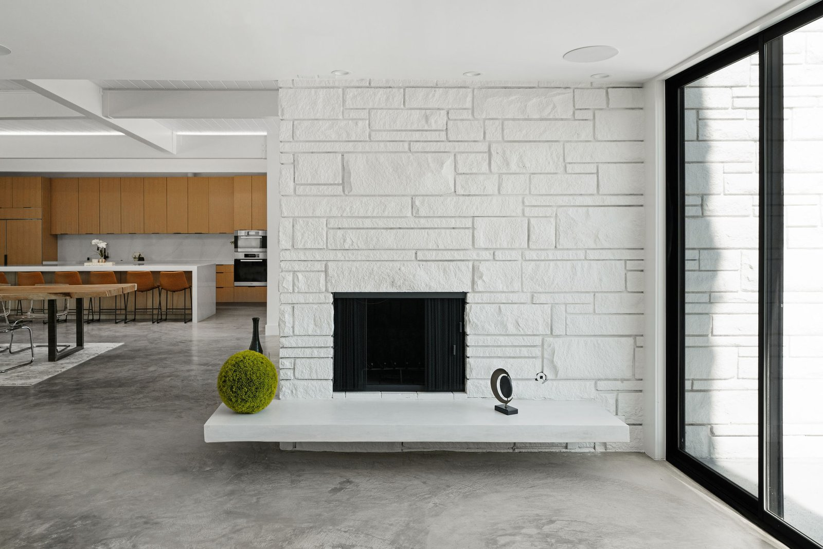 Today, the white-painted stone fireplace falls in line with the overall aesthetic.  Photo 18 of 25 in Before & After: Two Brothers List Their Swanky Midcentury Bachelor Pad for $1.6M