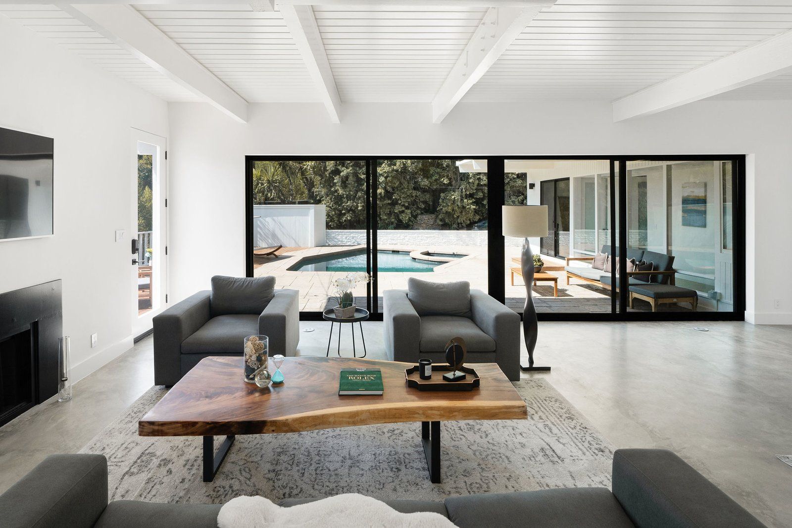 Across the back of the space, a new 22-foot Fleetwood sliding glass door overlooks the covered patio and backyard pool.  Photo 12 of 25 in Before & After: Two Brothers List Their Swanky Midcentury Bachelor Pad for $1.6M