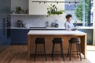 The kitchen, which was moved to the sunny side of the house, embraces Anyeley's taste for simple, modern forms. Cabinetry painted in Hague Blue by Farrow & Ball surrounds a central island fitted with Nerd bar stools by Muuto and a Dot Line Suspension pendant by Lambert & Fils. Completing the kitchen is a Litze faucet by Brizo and a Crosstown sink by Elkay, along with rangetop and wall ovens by Dacor and a Benchmark refrigerator from Bosch.