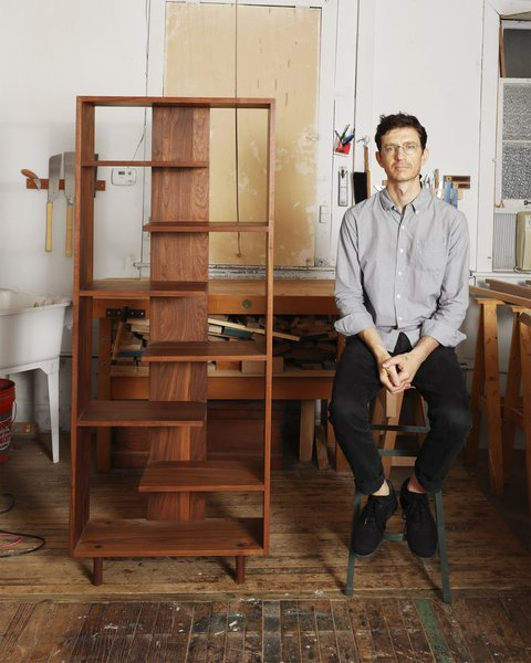 Designer Casey Lurie sits beside a piece from his Everyday Shelving project.
