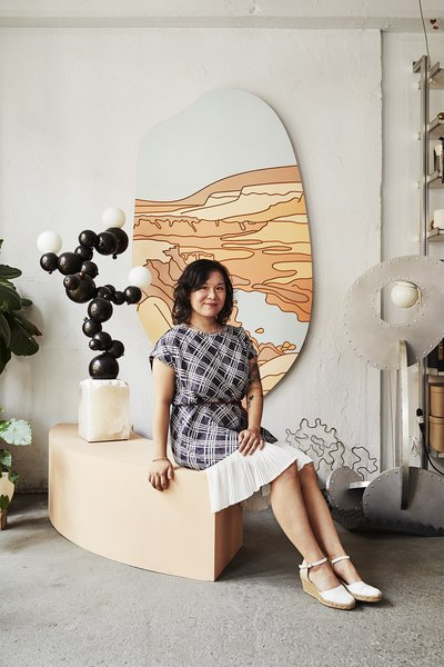 Rosie Li in her Brooklyn, New York, studio posing alongside her Bubbly Floor Lamp.