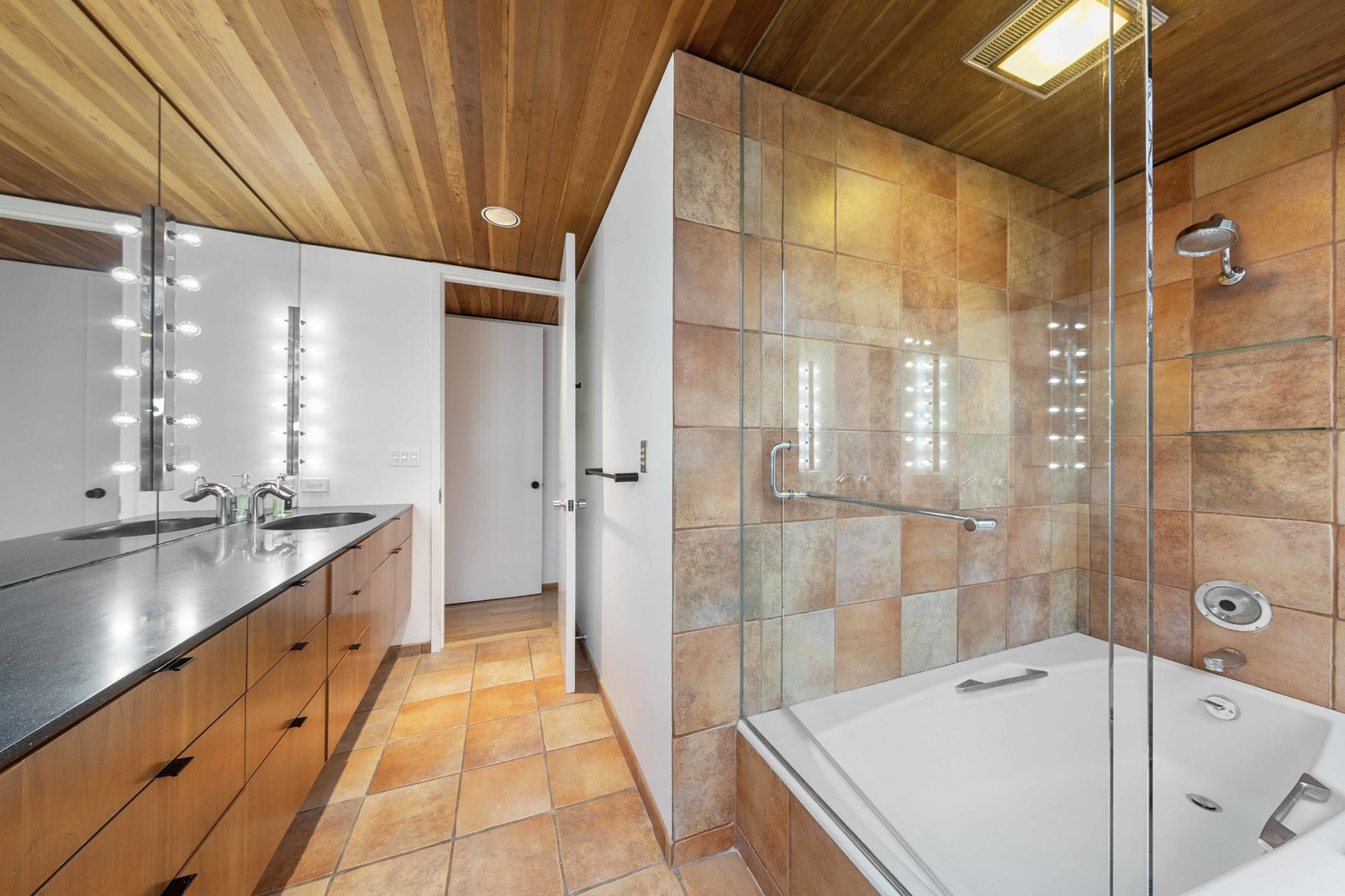 The attached bathroom offers a double vanity and large tub/shower.  Photo 9 of 15 in A Blackened Steel and Glass House Outside of Chicago Hits the Market for $825K