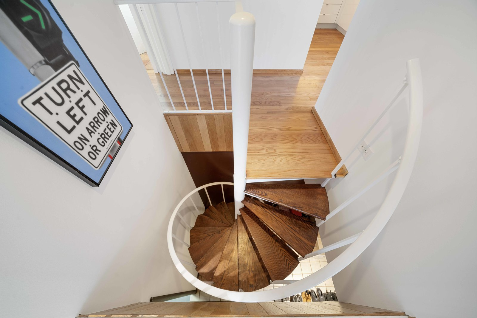 Back in the hallway near the kitchen, a spiral staircase leads down to the basement.  Photo 12 of 15 in A Blackened Steel and Glass House Outside of Chicago Hits the Market for $825K