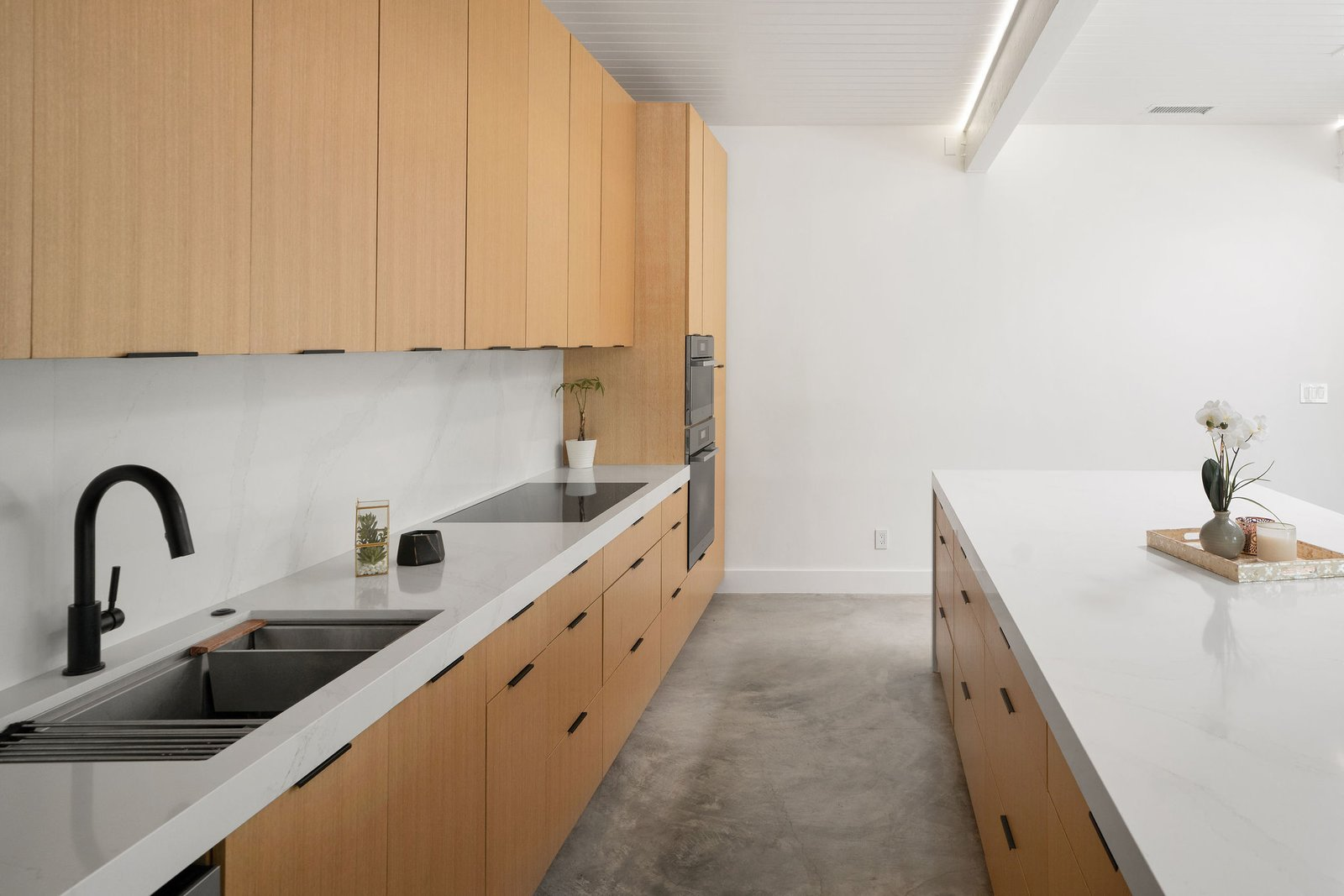 The space also features white oak cabinetry and quartz countertops, along with additional details such as LED lighting to illuminate the sides of each beam.  Photo 15 of 25 in Before & After: Two Brothers List Their Swanky Midcentury Bachelor Pad for $1.6M