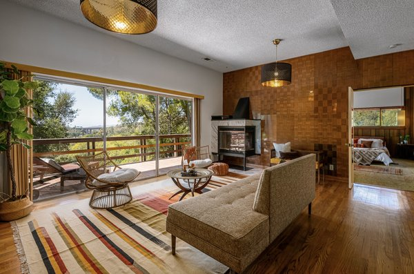 Another view of the family room reveals a fireplace, more wood paneling, and a large sliding glass door that leads to the outdoor space.