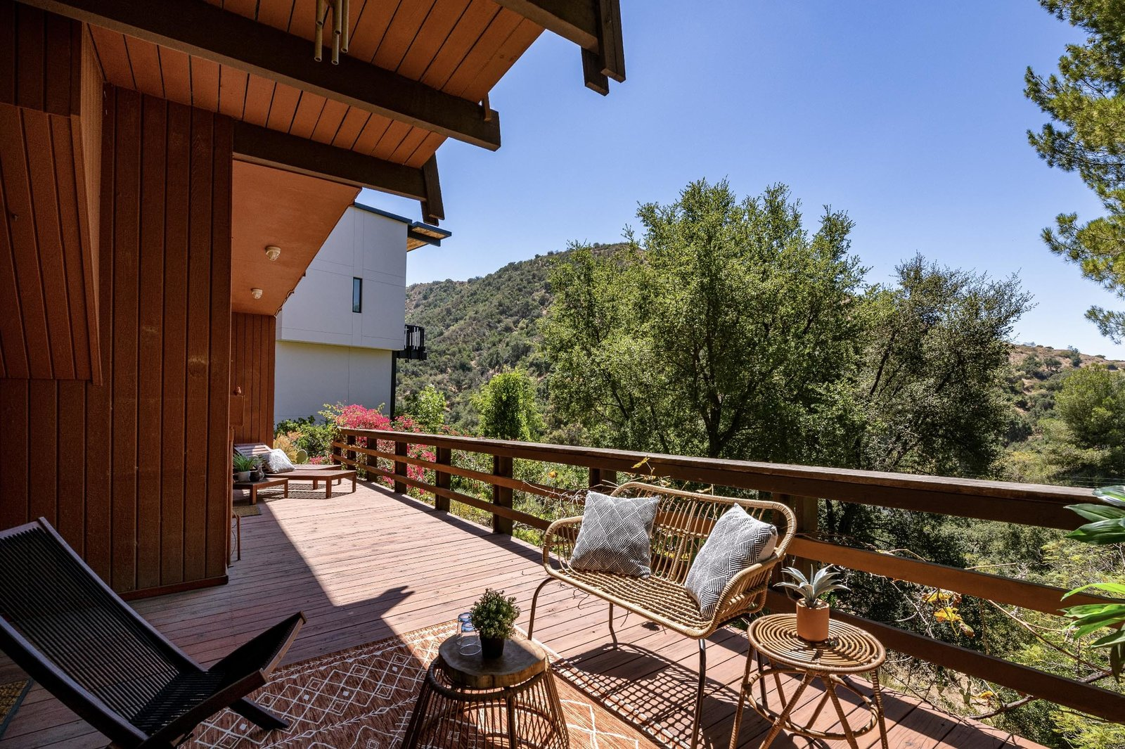 """The lower-level deck runs along nearly the entire width of the home and opens to the sloping lot at one end.  Photo 15 of 15 in This $1.2M California Midcentury House Looks Like It Came Straight Out of """"Mad Men"""""""