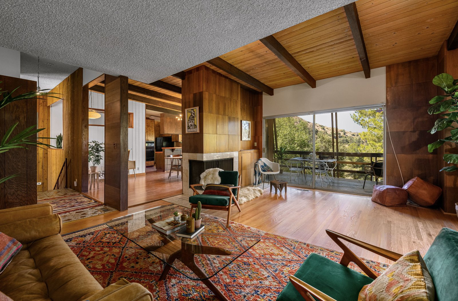 "A corner fireplace separates the living area from a formal dining room. Both the living room and dining are offer direct access to a covered balcony overlooking the canyon.  Photo 3 of 15 in This $1.2M California Midcentury House Looks Like It Came Straight Out of ""Mad Men"""