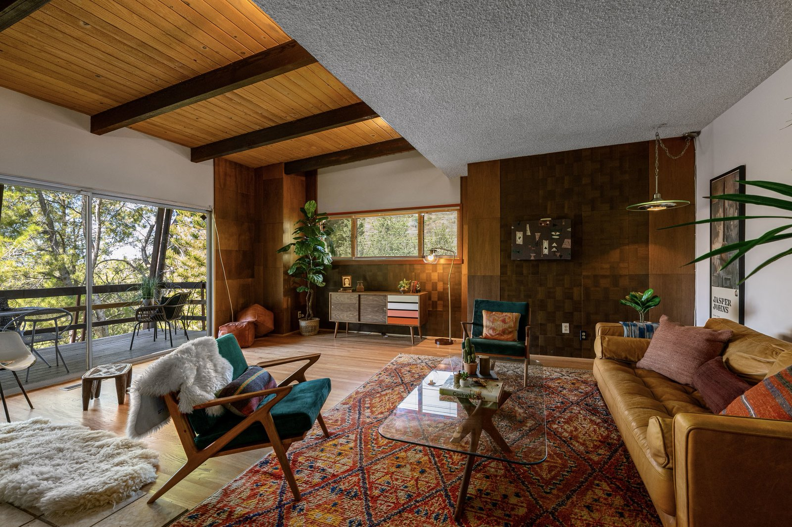 "Inside the front entryway, a living area fills one side of the upper level. Original beamed and wood-clad ceilings mix with original wood paneling and vintage light fixtures.  Photo 2 of 15 in This $1.2M California Midcentury House Looks Like It Came Straight Out of ""Mad Men"""