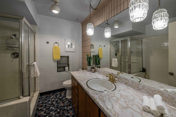 A look at one of two full bathrooms. The current owners updated this one by adding a mosaic of floor tile and painting a concrete block wall behind the vanity.