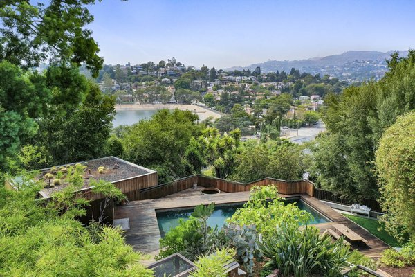 A view looking over vegetable beds shows the pool and guesthouse down below, as well as the Ivanhoe Reservoir and Hollywood Hills in the distance.