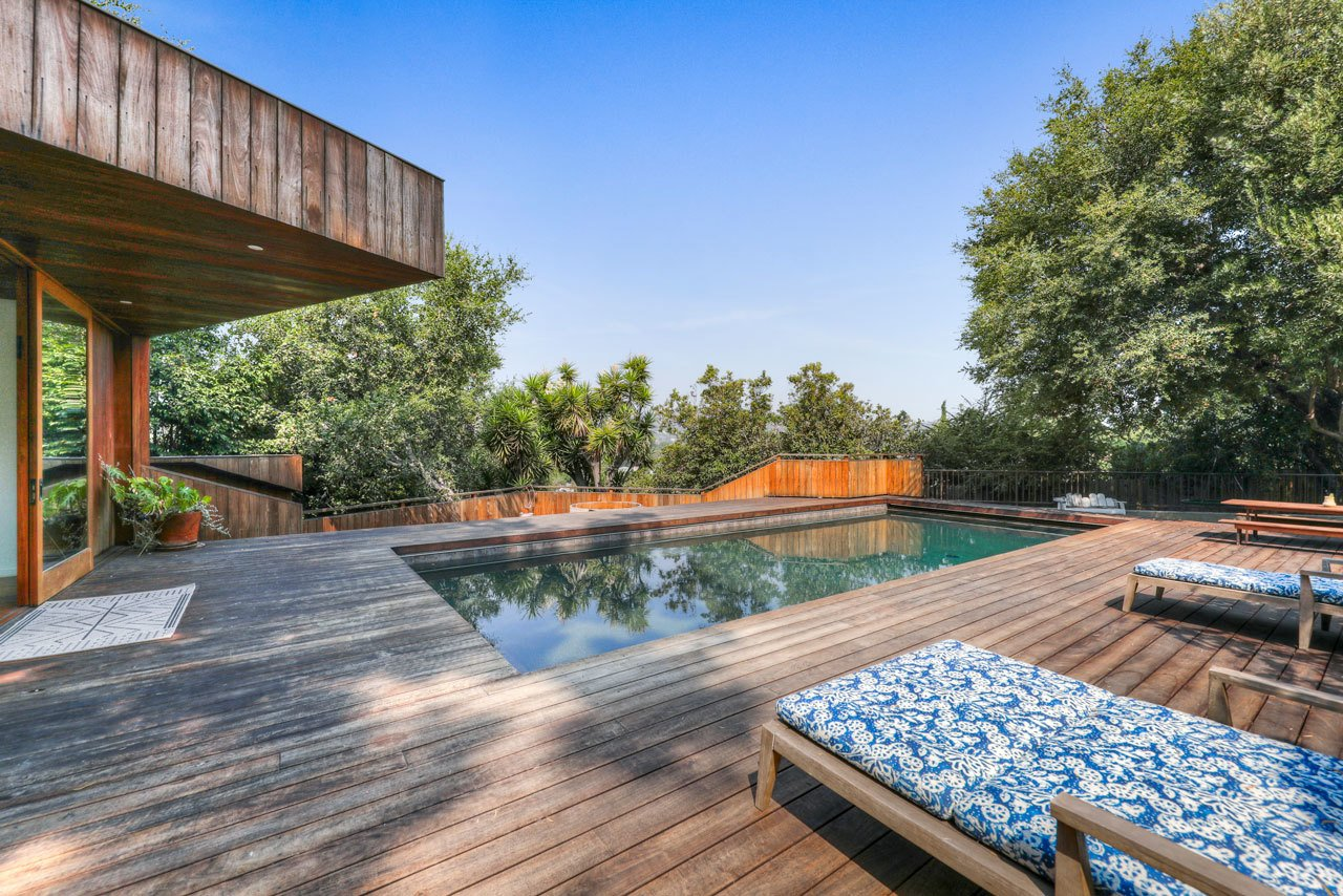 A large deck surrounds the pool at the bottom of the lot.
