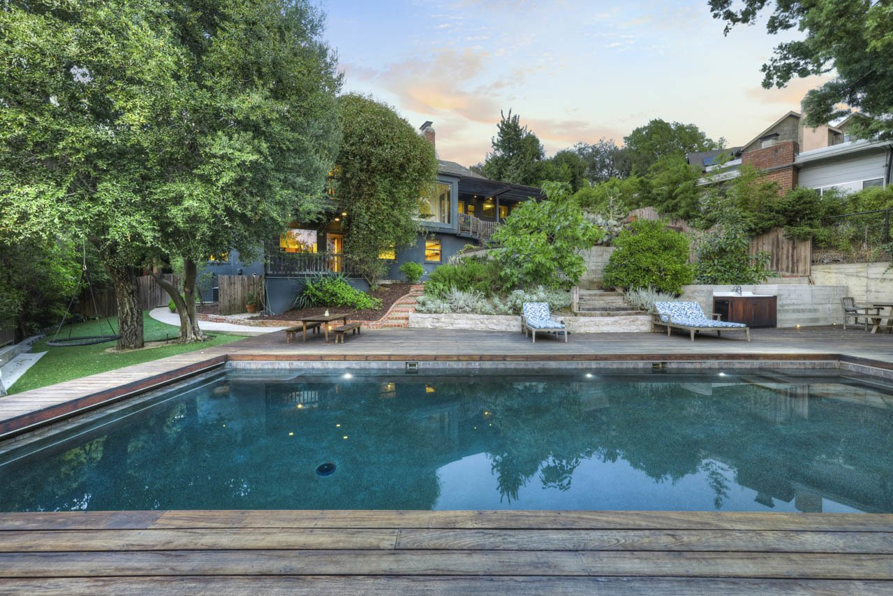 Another view of the pool area shows a small lawn along one side. A terraced area between the pool and house contains several fruit trees.  Photo 23 of 24 in Asking $3.75M, This Bohemian Hillside Home in L.A. Comes Complete With a Potter's Studio