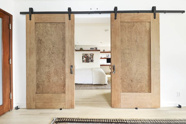 Barn-style doors divide the bedroom from a family room and office.