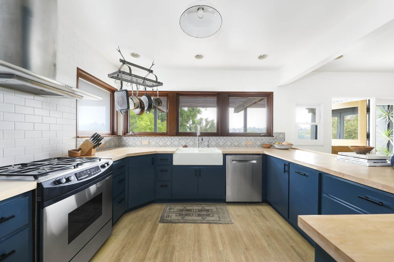 Kitchen Opposite from the dining area the brightly lit kitchen features colored cabinetry and wood countertops.  Photo 6 of 24 in Asking $3.75M, This Bohemian Hillside Home in L.A. Comes Complete With a Potter's Studio