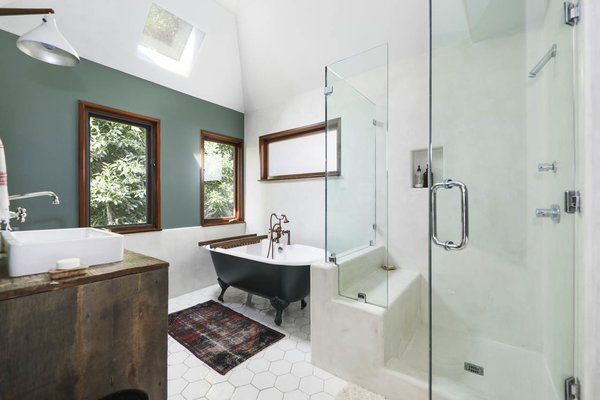 The master bathroom features a clawfoot tub, custom vanity, and glass-walled shower. A skylight illuminates the space from above.