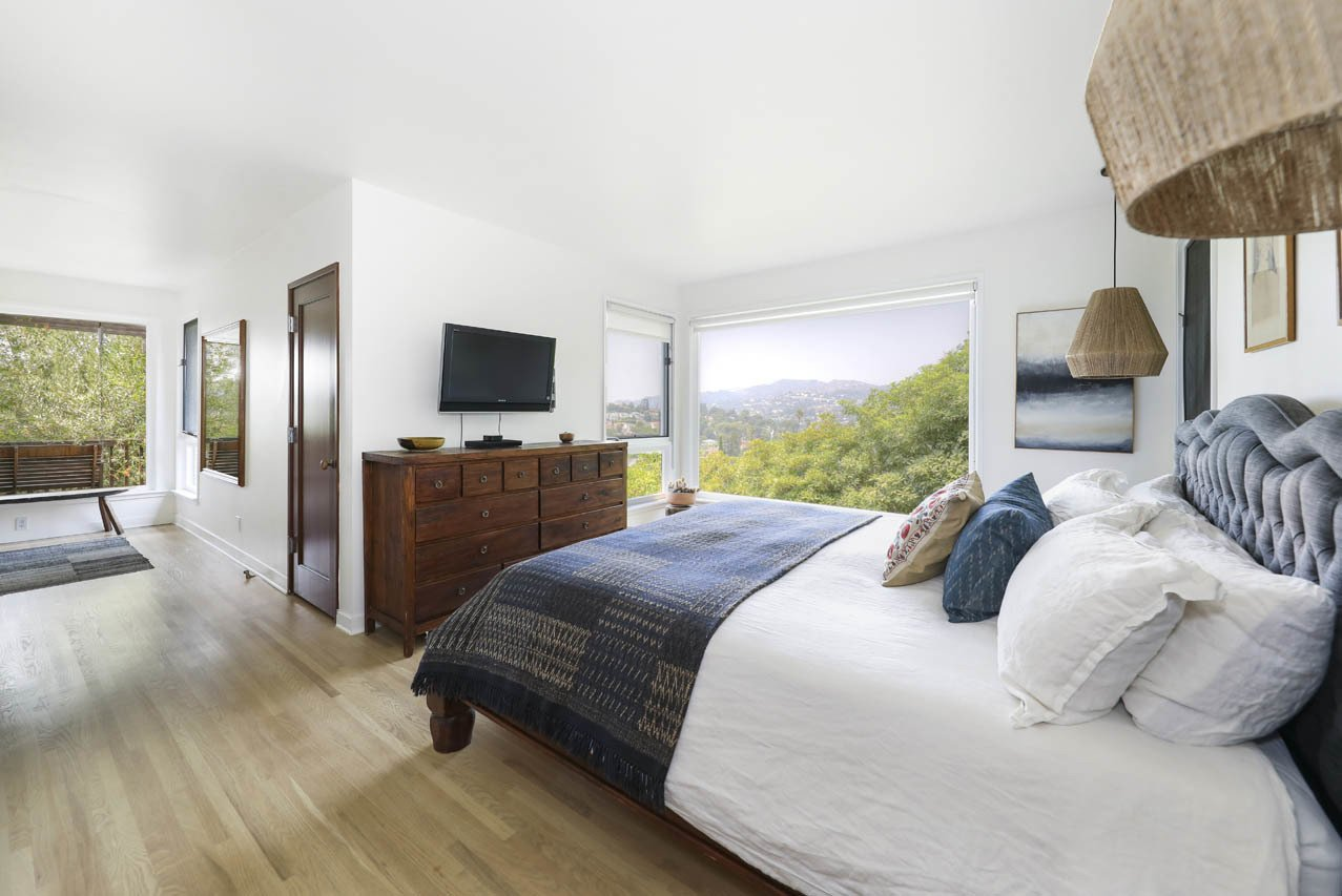 In the master bedroom, a large picture window frames a view of the surrounding hills.  Photo 8 of 24 in Asking $3.75M, This Bohemian Hillside Home in L.A. Comes Complete With a Potter's Studio