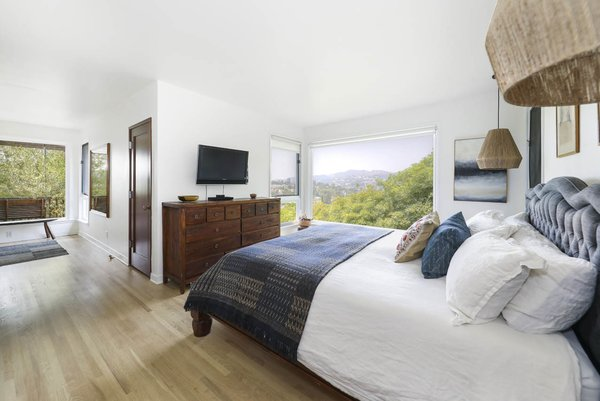 In the master bedroom, a large picture window frames a view of the surrounding hills.