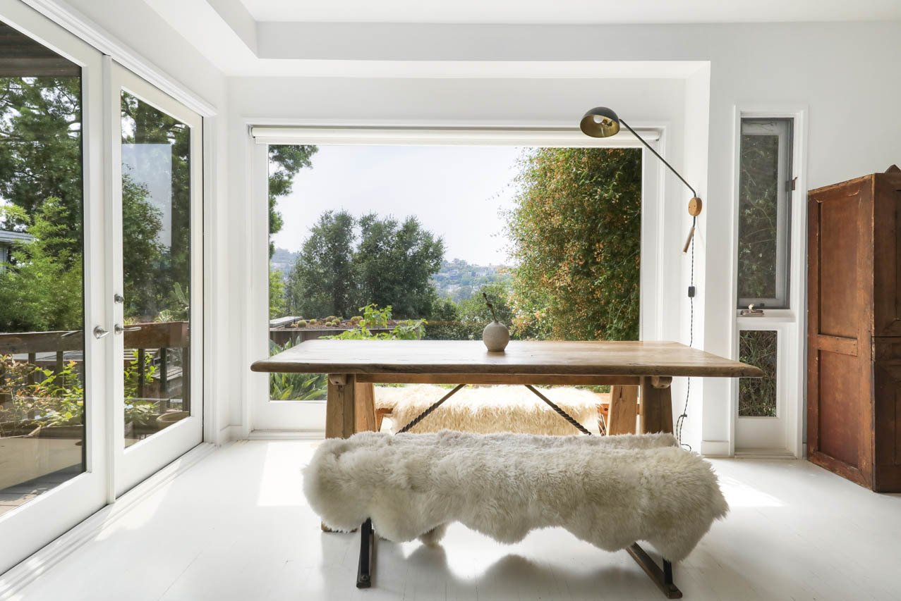 Dining Room, Bench, Table, and Wall Lighting French doors lead out to a porch and down to the poolside patios.  Photo 4 of 24 in Asking $3.75M, This Bohemian Hillside Home in L.A. Comes Complete With a Potter's Studio