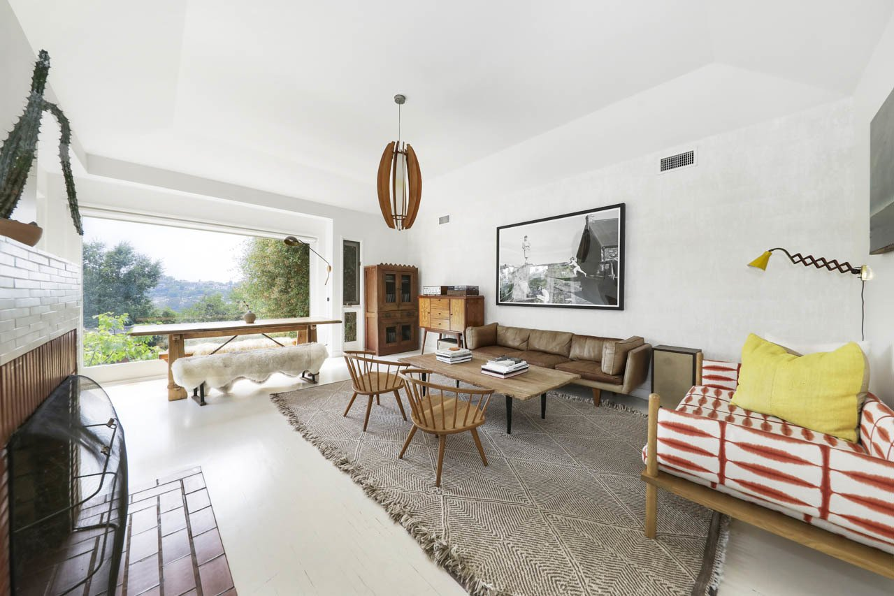 Living Room, Coffee Tables, Chair, Pendant Lighting, Sofa, and Standard Layout Fireplace Another view of the living area reveals the large picture window at one end.  Photo 3 of 24 in Asking $3.75M, This Bohemian Hillside Home in L.A. Comes Complete With a Potter's Studio