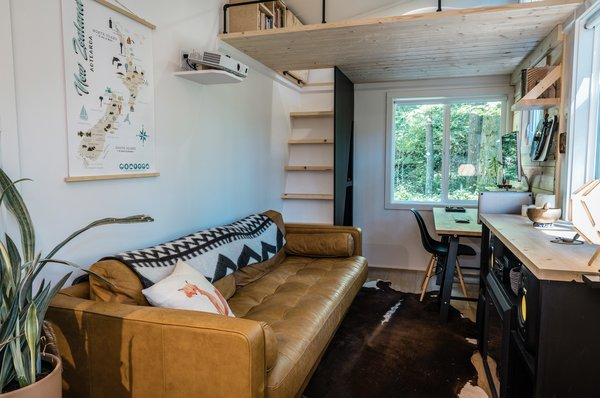 Inside, the approximately 330-square-foot space features two lofts at either end. The home is currently outfitted with a mix of designer furnishings, which can be negotiated in the sale.