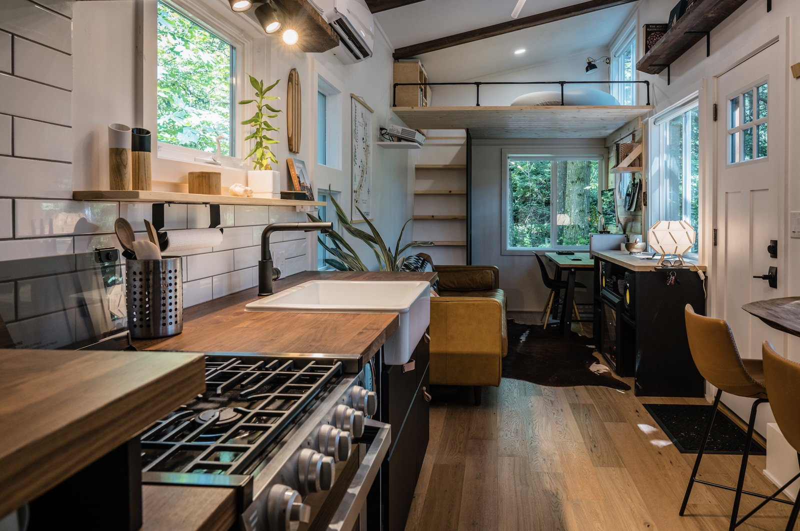 Both the interior and exterior of this Japandi tiny home feature contrasting shades of black and natural wood tones, which homeowner Stephen Proctor first imagined after picking up a Theo coffee mug and teapot by the brand Stelton. The matte-black ceramic base and simple bamboo handle and lid inspired him to mimic the combination throughout the tiny home.  Photo 7 of 11 in A Furnished Tiny Home With Japanese and Scandinavian Vibes Is Offered at $99K