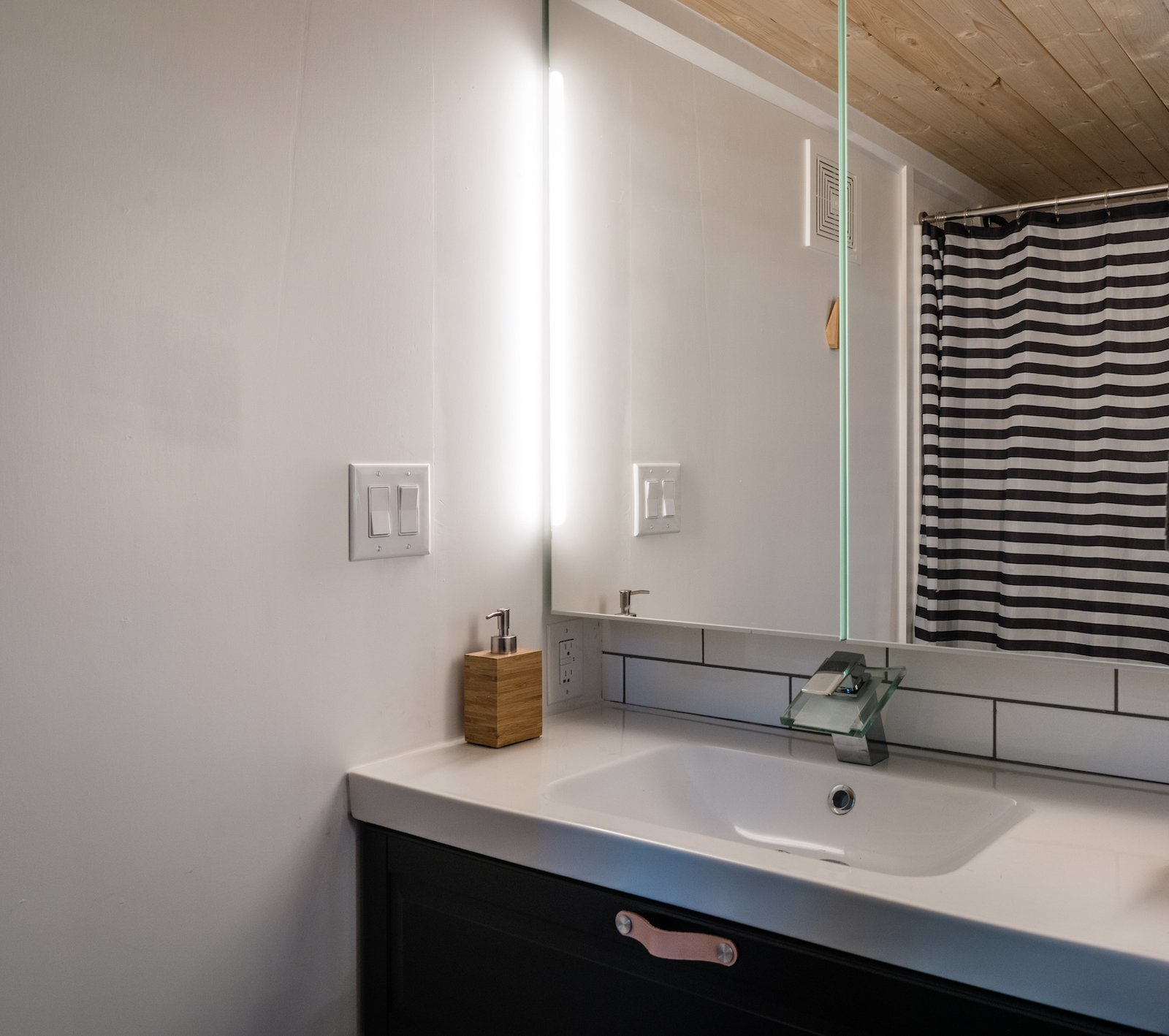 A full bathroom along the back of the lower level features a shower and toilet outfitted for septic hookup. The space also features a washer/dryer unit in the opposite corner.  Photo 8 of 11 in A Furnished Tiny Home With Japanese and Scandinavian Vibes Is Offered at $99K