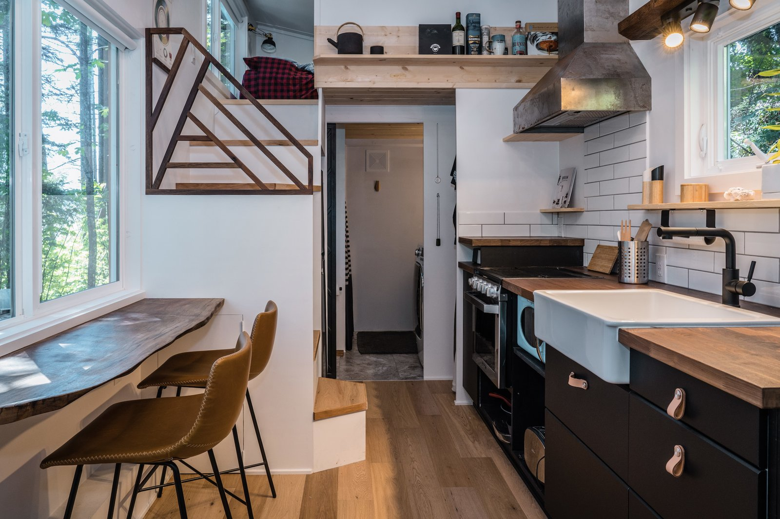 A closer look at the kitchen area, where leather cabinet pulls and open shelving complement wood counters and a custom stair railing. Stephen's inspirational tea pot and mug sit along a shelf above the bathroom doorway.  Photo 5 of 11 in A Furnished Tiny Home With Japanese and Scandinavian Vibes Is Offered at $99K