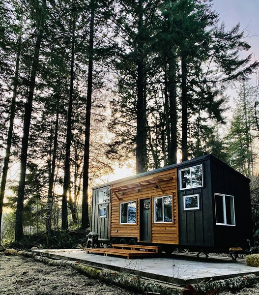 Less than a year old, this tiny house is up for sale in the Pacific Northwest near Portland, Oregon. The 31-foot-long, 8.5-foot-wide structure features a contrasting facade of natural cedar and painted board-and-batten siding.
