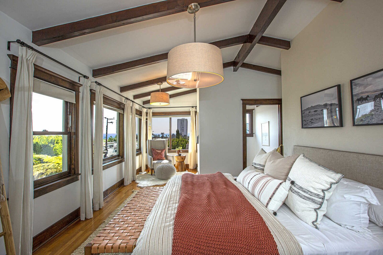 "Upstairs, the principal suite comes with exposed beams and a wall of windows, as well as a seating area in the corner.  Photo 11 of 14 in ""Last Man on Earth"" Creator Will Forte Puts His Santa Monica Craftsman on the Market for $2.45M"