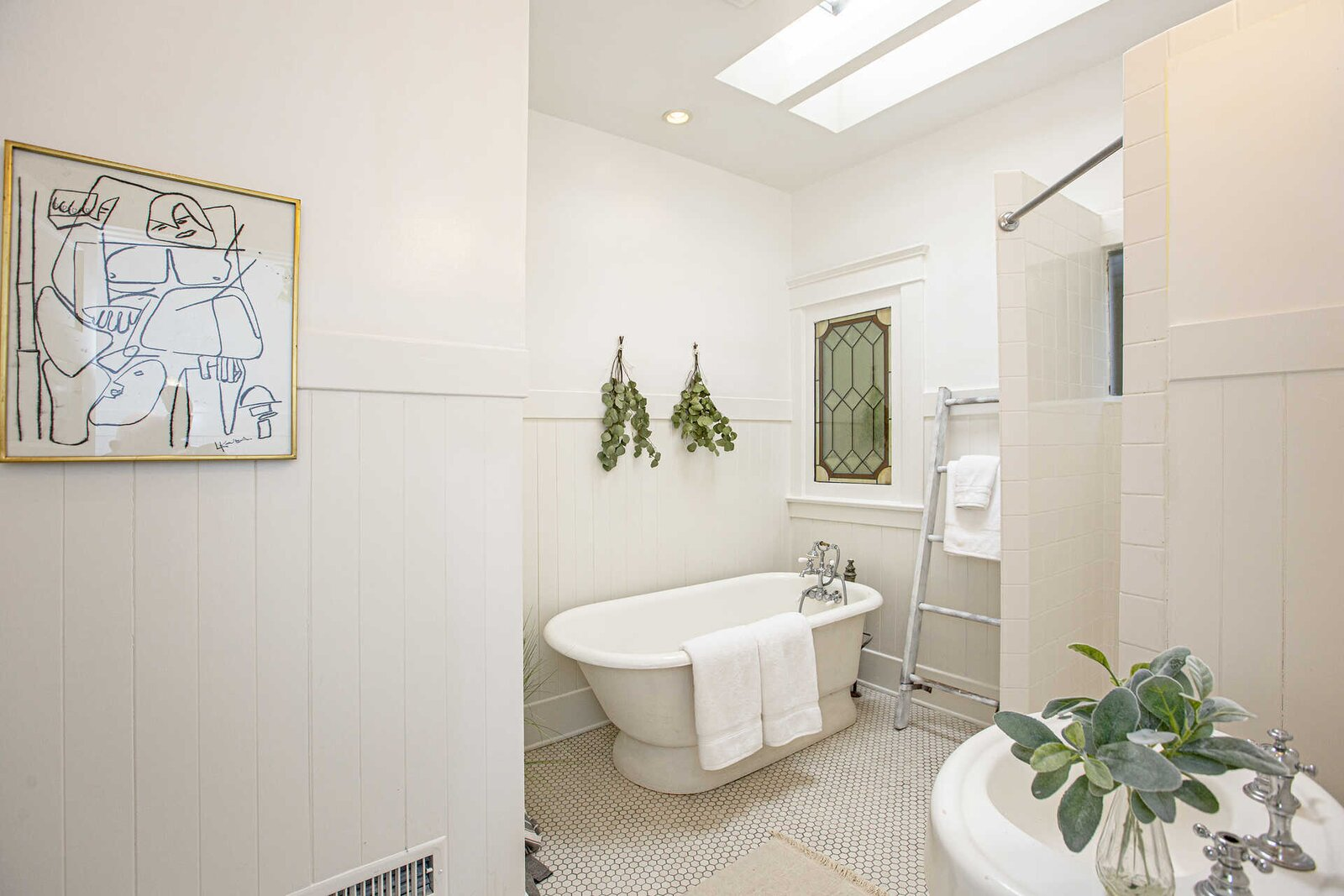 """The adjacent bathroom is also illuminated by a skylight above the shower and soaking tub. A stained-glass window, pedestal sink, and tile floors add additional character.  Photo 9 of 14 in """"Last Man on Earth"""" Creator Will Forte Puts His Santa Monica Craftsman on the Market for $2.45M"""
