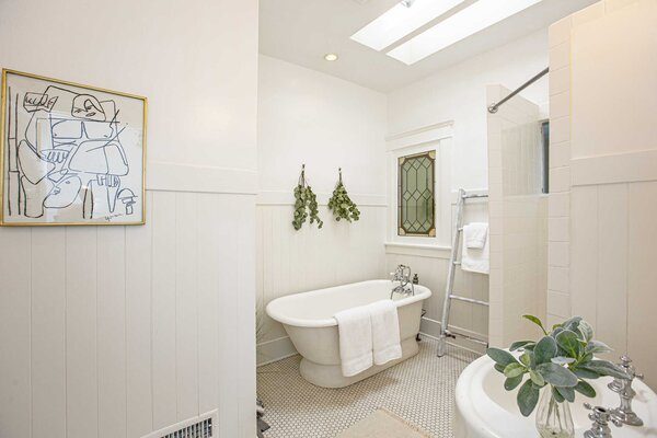 The adjacent bathroom is also illuminated by a skylight above the shower and soaking tub. A stained-glass window, pedestal sink, and tile floors add additional character.