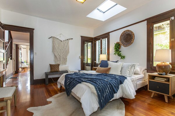 Opposite the dining area and just off the living room, a sunlit bedroom features windows on each side of the bed and a skylight above.
