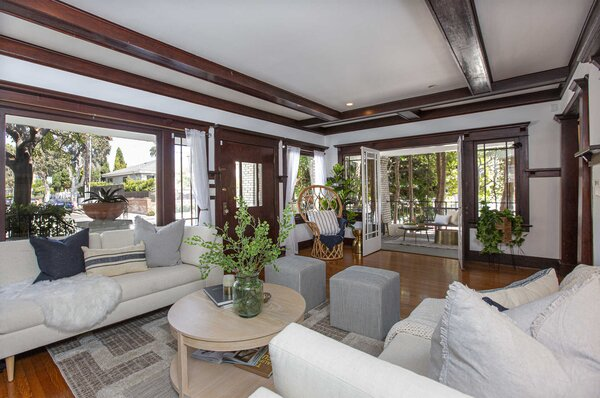 Inside, the front door opens into a large living area that runs along the front of the home. Traditional Craftsman features abound in the space—most notably the original beamed ceilings and extensive moldings.