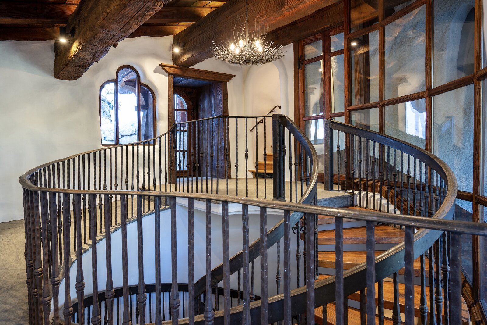 """One one side of the home, a spiral staircase leads down to the lower level. Some of the home's custom railings were refinished/replaced during the recent renovation.  Photo 9 of 15 in Listed for $2.65M, This Bavarian-Style """"Snow Haus"""" Near Lake Tahoe Is the Perfect Alpine Escape"""