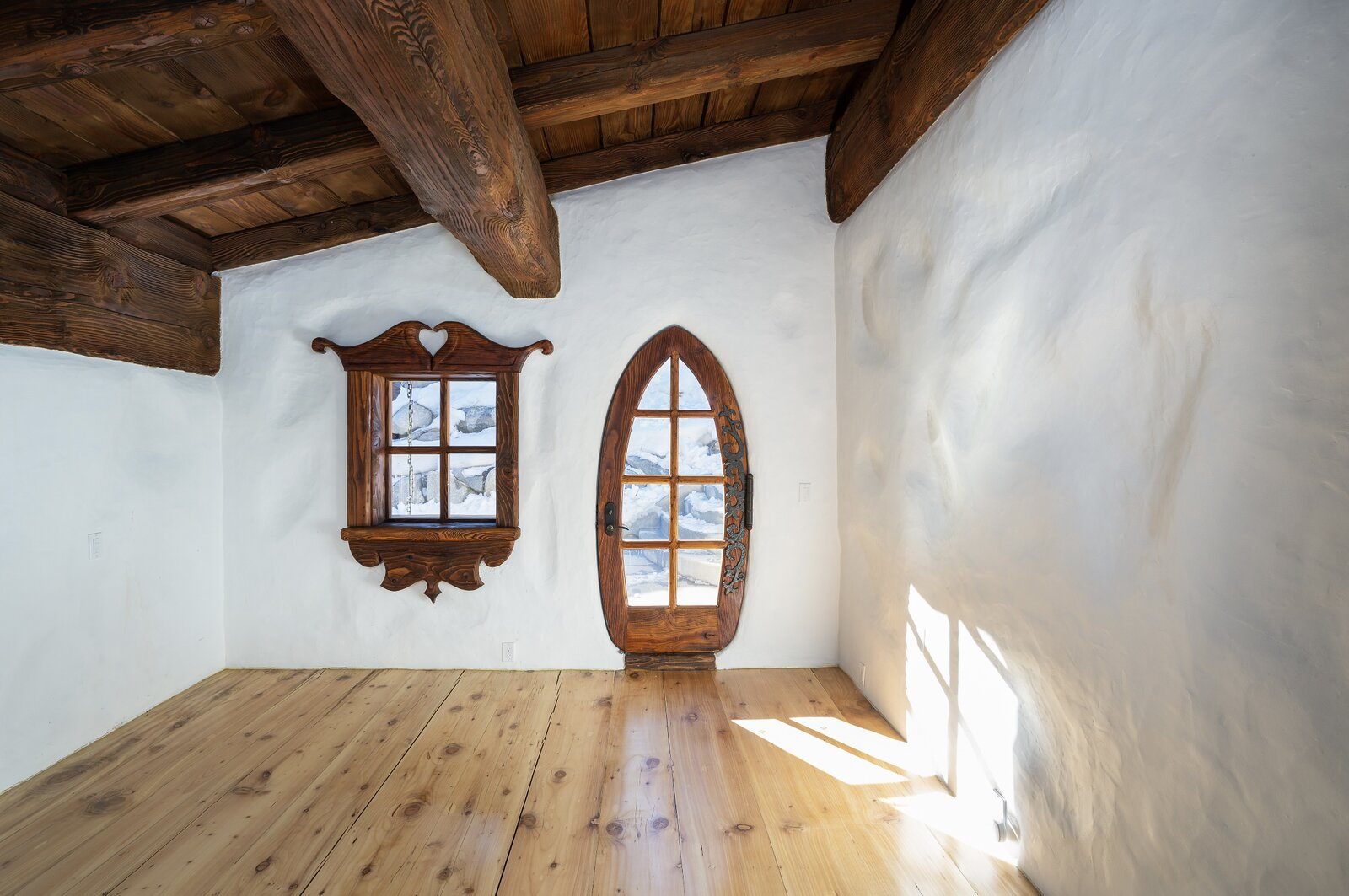"All of the home's seven bedrooms feature intricate window trim and other wood details. Here, one bedroom comes with a whimsically shaped door that provides direct access to the exterior.  Photo 6 of 15 in Listed for $2.65M, This Bavarian-Style ""Snow Haus"" Near Lake Tahoe Is the Perfect Alpine Escape"