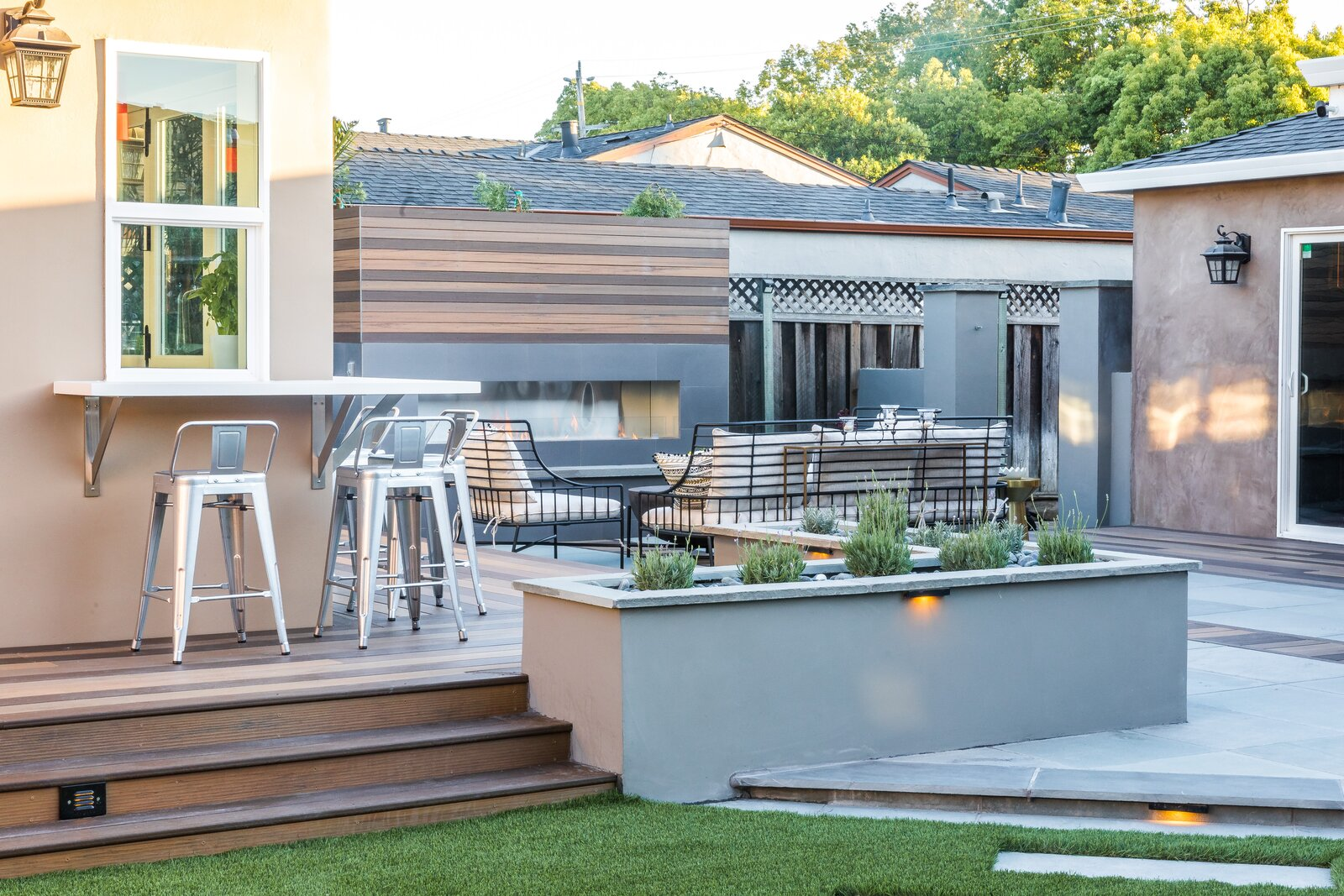 Outdoor, Large Patio, Porch, Deck, Back Yard, Shrubs, Raised Planters, Decking Patio, Porch, Deck, Stone Patio, Porch, Deck, Grass, Hardscapes, and Trees The technology behind TimberTech's products recreates the look of real wood, with various steps to produce the variation found in natural products as well.  Photo 6 of 8 in From Trash to Treasure, You Can Build a Deck That's Easy on Both the Eyes and the Environment