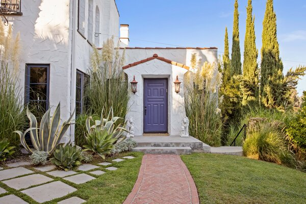 A brick walkway leads to the front door. The home's exterior is typical of the Spanish Revival style, with a stuccoed facade, wrought-iron details, and a tile roof.