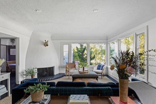 The front door opens in to a sunlit living area with a Spanish-style kiva fireplace in one corner. A wall of windows wrap around another corner.