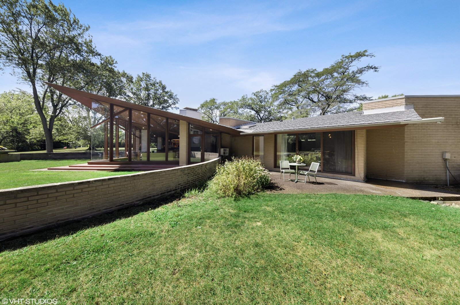 Outside a large lawn surrounds the home and several patios. Here, an outdoor area near the principal bedroom is separated by a semicircular brick wall that extends from both sides of the living room's glass facade.  Photo 12 of 14 in A Big and Bright Midcentury Home by Frank Lloyd Wright Apprentice Don Erickson Asks $595K