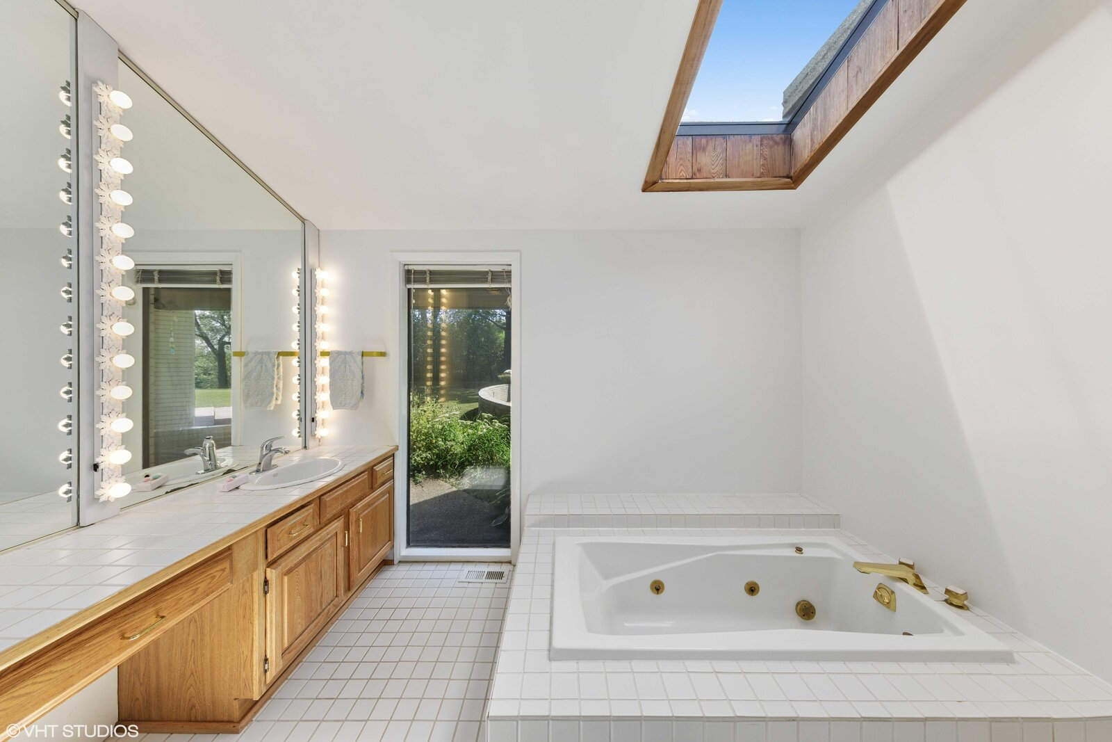 The adjoining bathroom offers a floor-to-ceiling window and skylight.  Photo 9 of 14 in A Big and Bright Midcentury Home by Frank Lloyd Wright Apprentice Don Erickson Asks $595K