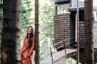Sally Aano next to one of the two recently completed tree houses.