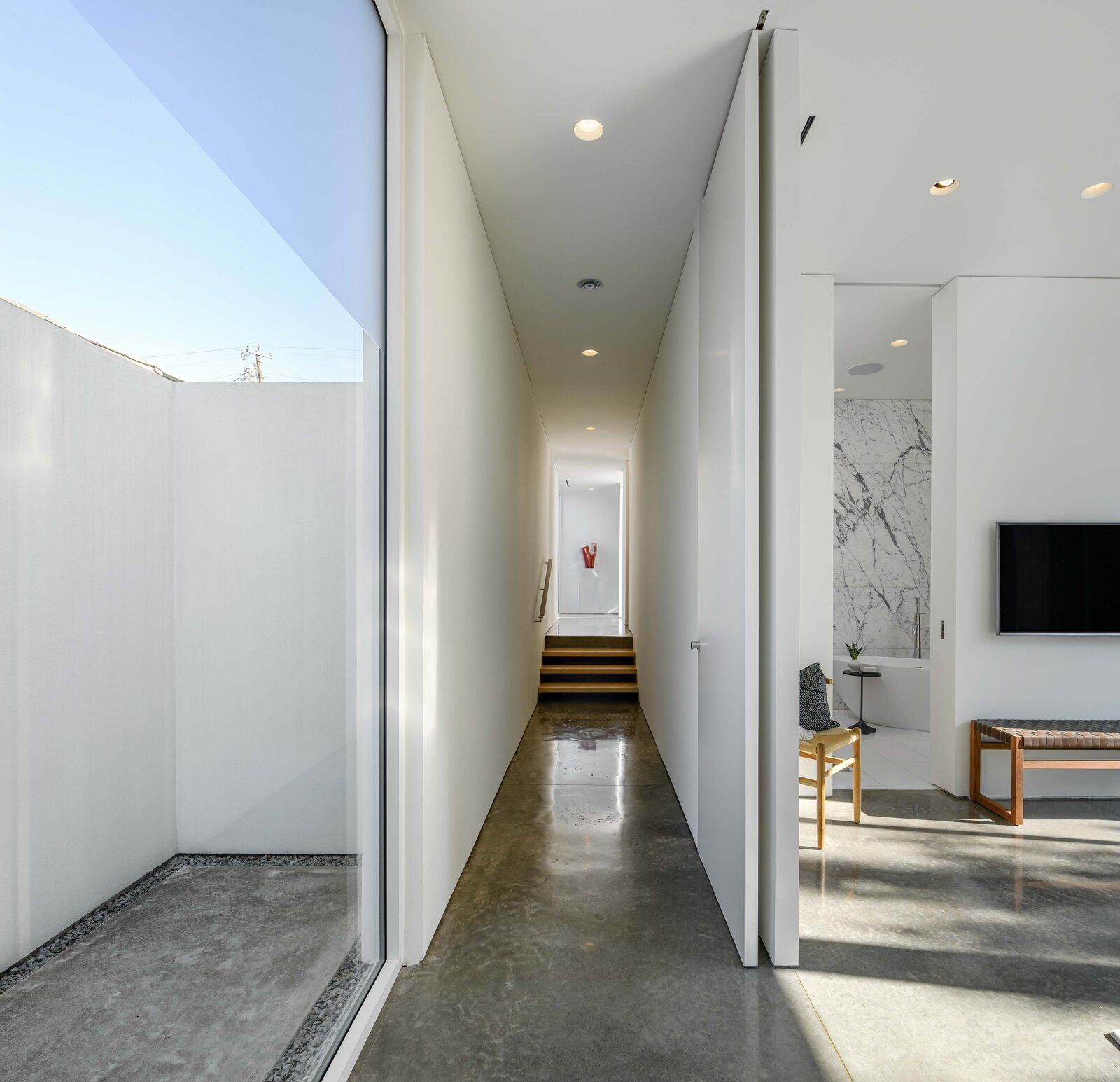 Hallway and Concrete Floor Along one side of the home, a long hallway provides access to the principal suite, while an enclosed outdoor space provides privacy for a floor-to-ceiling window along one wall.  Photo 6 of 11 in A Chic Urban Retreat by Modernist Architect Lionel Morrison Asks $2.5M in Dallas